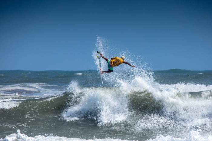 italo ferreira surfer wave yellow jersey aerial