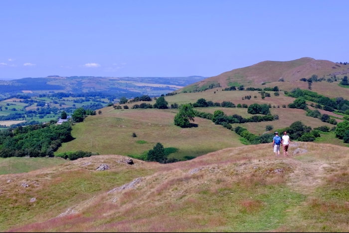 couple walking in hills with blue sky